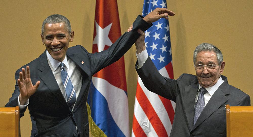 Raúl Castro, presidente cubano, levanta la mano de Barack Obama, presidente de EEUU