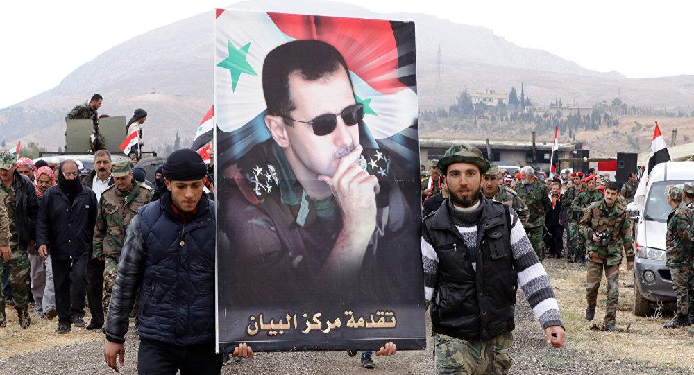 Voluntarios sirios llevan la imagen del presidente del país, Bashar Asad