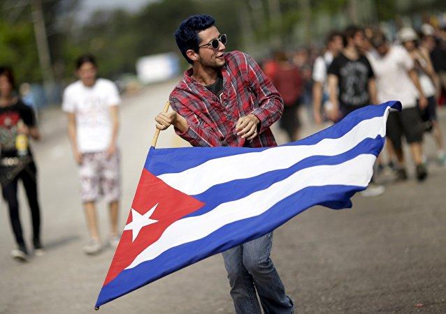 Un joven con una bandera cubana a las afueras de la Ciudad Deportiva