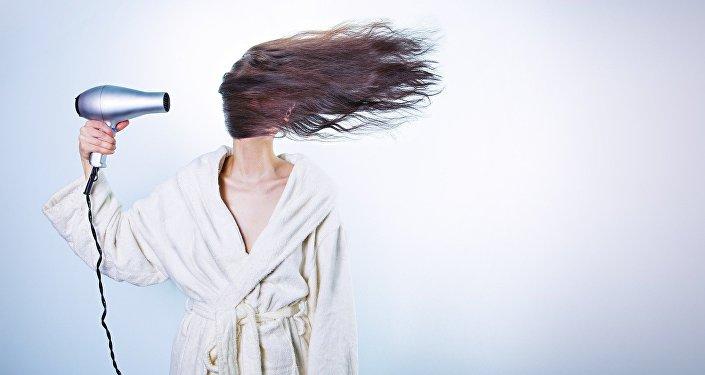 Una mujer con un secador de cabello