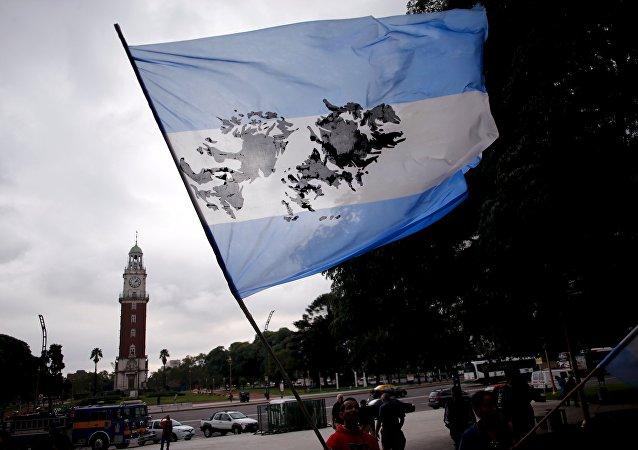 Un hombre sostiene una bandera argentina con la imagen de las Islas Malvinas.