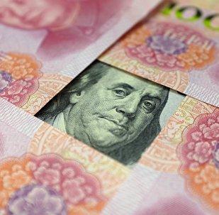 Yuanes chinos y un billete de dólar
