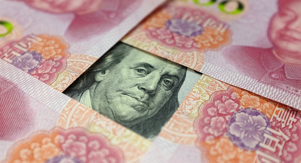 A US 100-dollar banknote with a portrait of Benjamin Franklin and Chinese 100-yuan banknotes with portrait of late Chinese Chairman Mao Zedong are seen in the picture illustration in Beijing, China