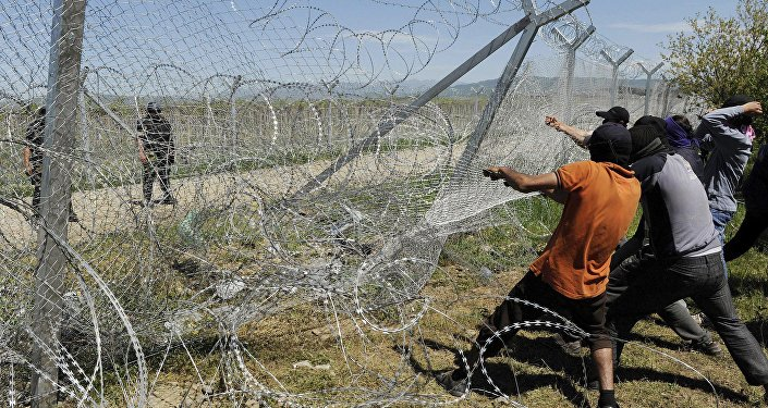 Migrantes intentan derrumbar una parte de la valla fronteriza entre Grecia y Macedonia (archivo)