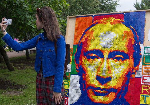 Una joven toma selfie en frente del retrato de Putin en el festival de las redes sociales