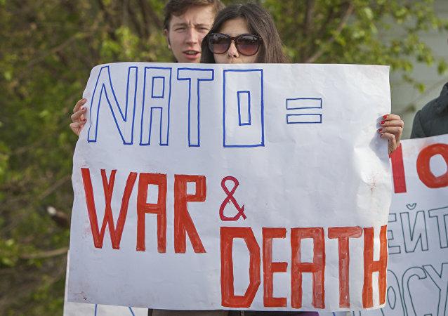 Activistas sosteniendo carteles anti-OTAN