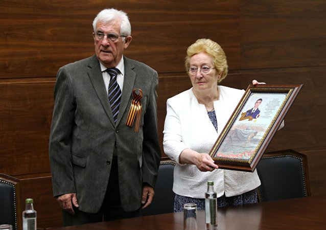 Jean Claude y Michelin Magues otorgaron las condecoraciones militares de sus antepasados a la familia del soldado ruso caído en Siria, Alexandr Projorenko