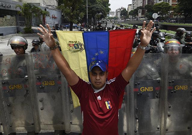 Un manifestante con la bandera nacional de Venezuela