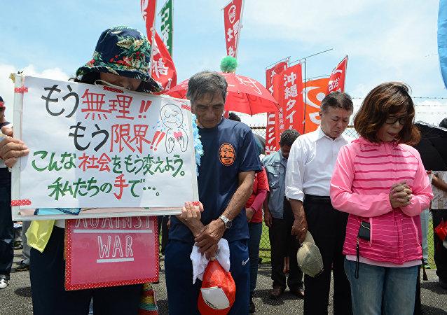 Gente rezando en protesta contra la presencia militar de EEUU en Okinawa