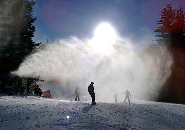 Los snowboardistas cerca de un cañón de nieve