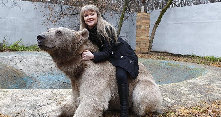 El oso Stepán juega con Svetlana en el Parque Losiny Ostrov