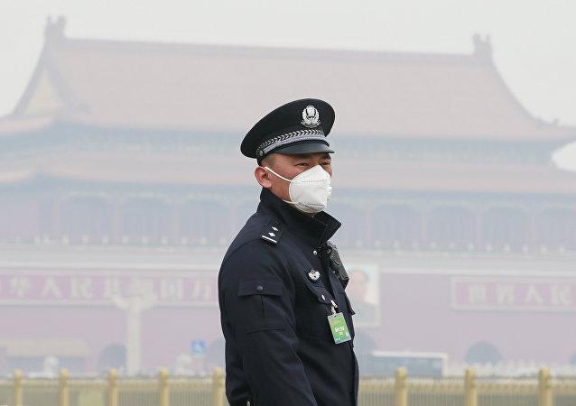 Policía chino con una máscara respiratoria