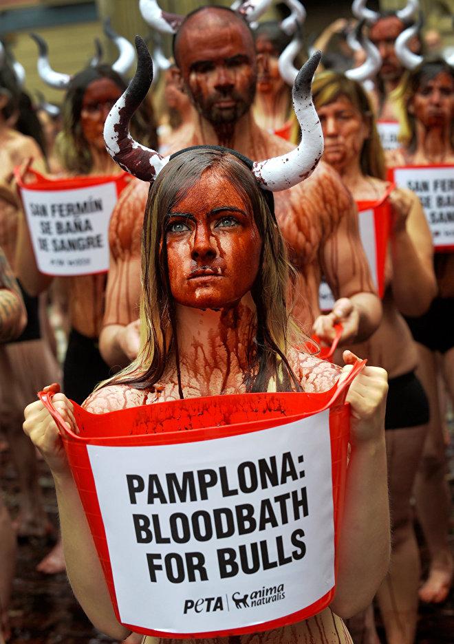 Una manifestante porta un cubo lleno de 'sangre' para protestar contra el maltrato a los toros en las fiestas de San Fermín. Pamplona, España, 5 de julio de 2016.