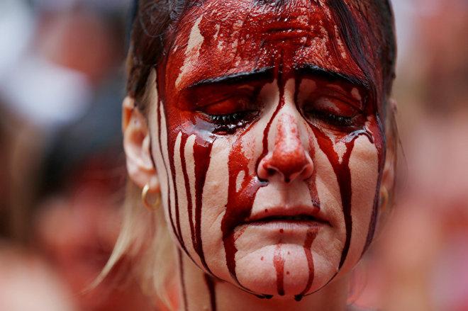 Manifestante cubierta de 'sangre' durante las protestas contra los encierros en las tradicionales celebraciones regionales de San Fermín. Pamplona, España, 5 de julio de 2016.