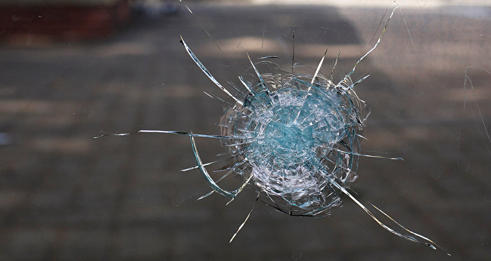 Broken glass from a bullet hole is seen at a bus stop near the shooting scene in Dallas, Texas, U.S