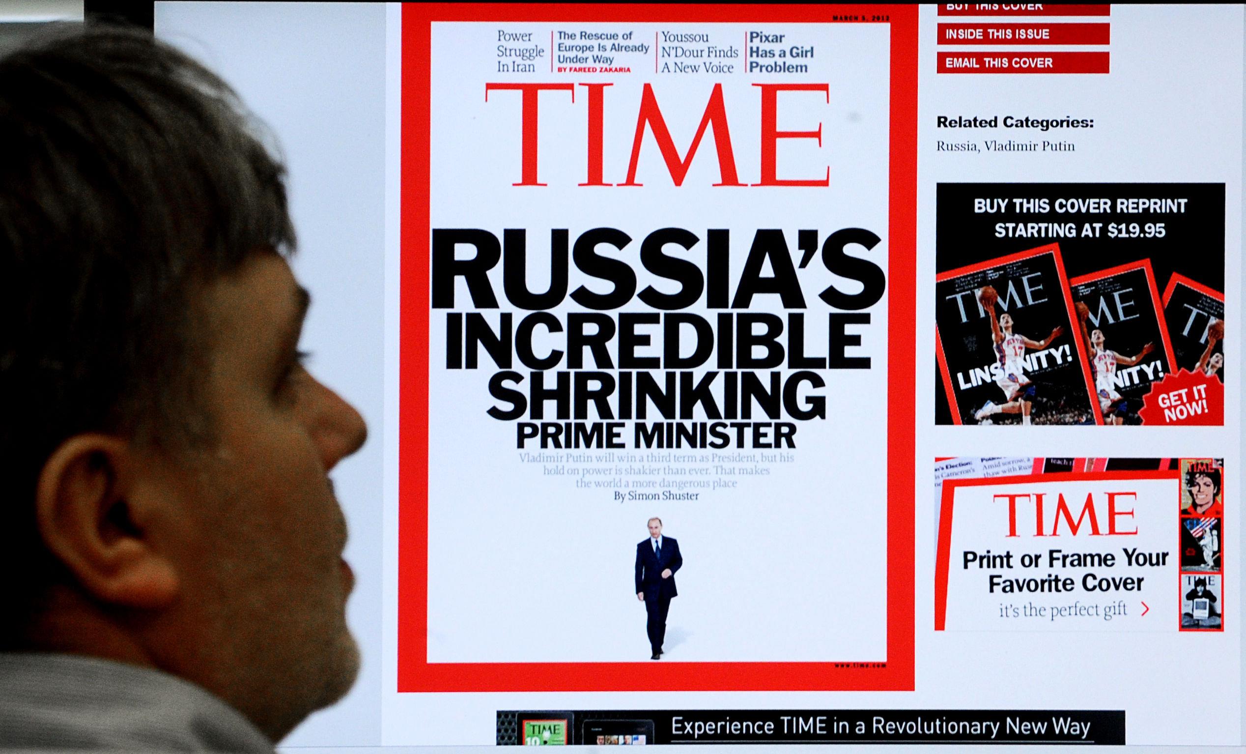 Un hombre examinando la portada de la revista estadounidense Time