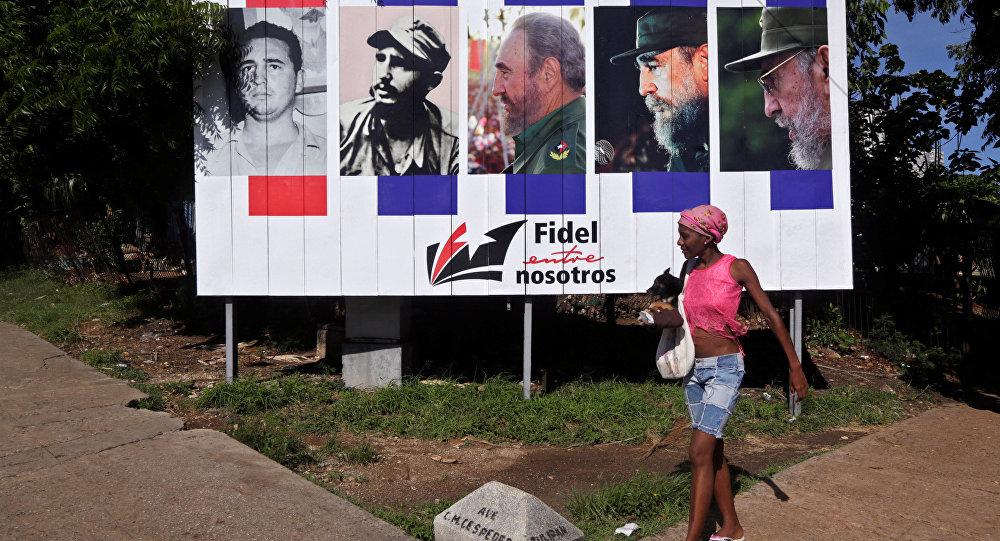 Mujer pasa junto a la pancarta Fidel con nosotros, Cuba
