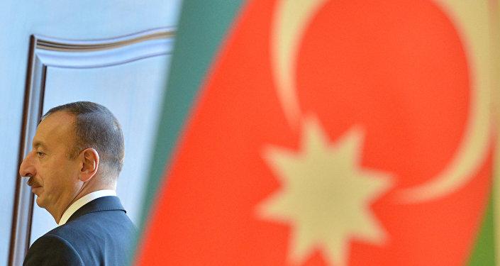 El presidente de Azerbaiyán, Ilham Aliyev, y la bandera del país (archivo)