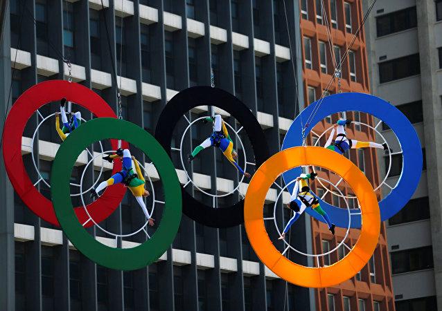 Acróbatas actúan en los anillos de los Juegos Olímpicos en el centro financiero de Sao Paulo, Brasil