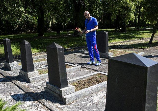 Un hombre deposita flores en una tumba