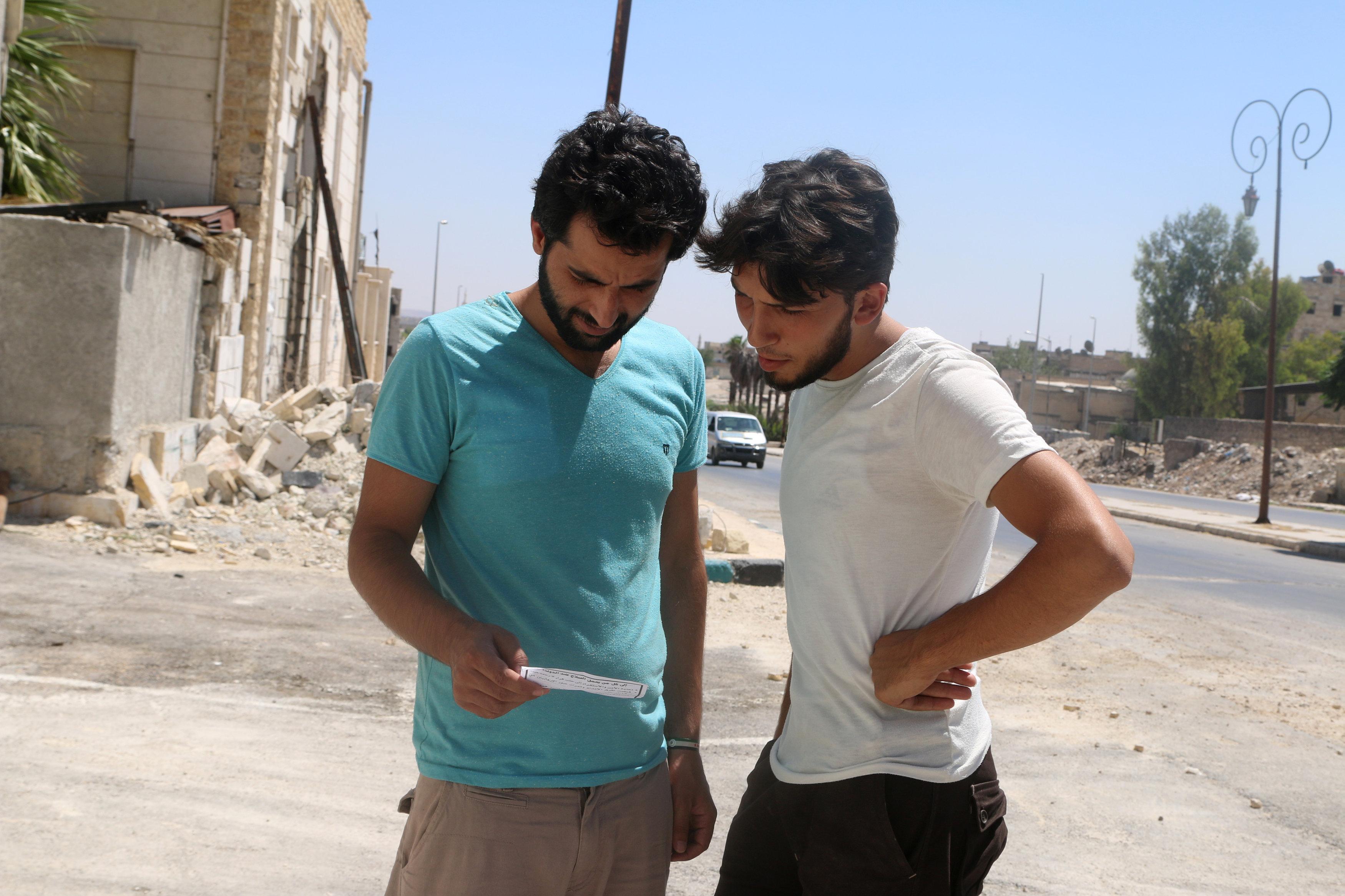 Vecinos de Alepo leen uno de los folletos lanzados por el Ejército sirio sobre los distritos de la urbe, pidiendo a los residentes cooperar con los militares y exigiendo a los rebeldes deponer las armas. Siria 28 de julio de 2016.