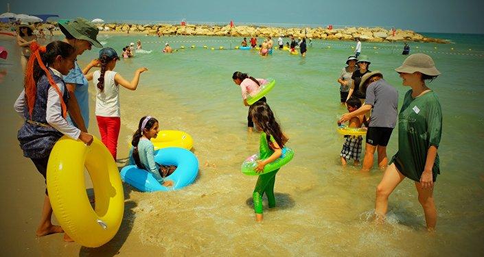 Voluntarios de la ONG Min el Bahar ayudan a niños palestinos a meterse en el agua, en la playa de Tel Baruch, en Tel Aviv