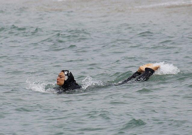 Mujer musulmana nada en burkini
