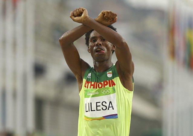 Lilesa cruzando la meta y haciendo un gesto como si tuviera los brazos esposados, en señal de protesta contra la persecución del Gobierno etíope contra la etnia oromo