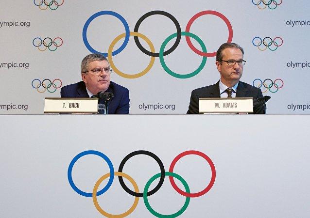 El Presidente del Comité Olímpico Internacional Thomas Bach (a la izquierda) y el Director de Comunicaciones Mark Adams (a la derecha)