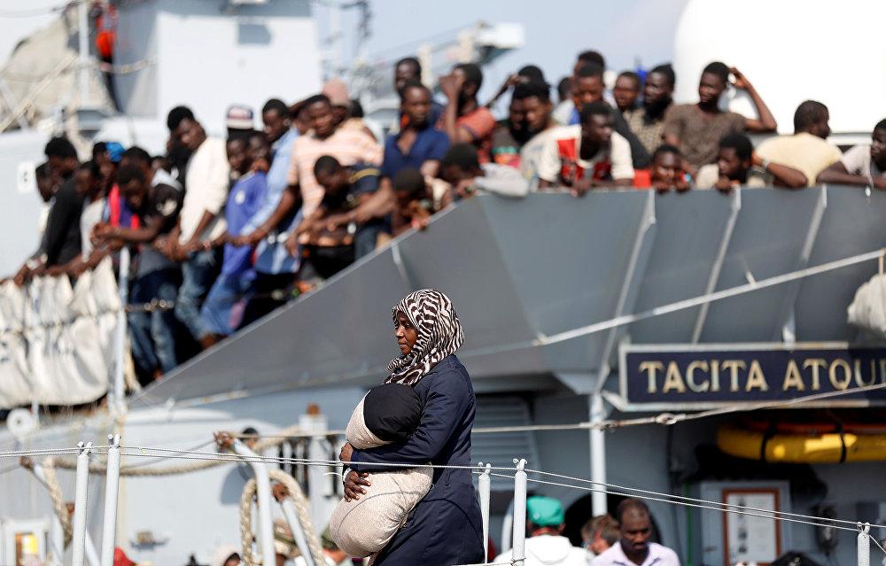 Una mujer sale de una nave marina italiana en el puerto de Pozzallo, Italia.