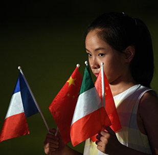 Una niña sostiene las banderas de los países miembros del G20 en la cumbre en Hangzhou