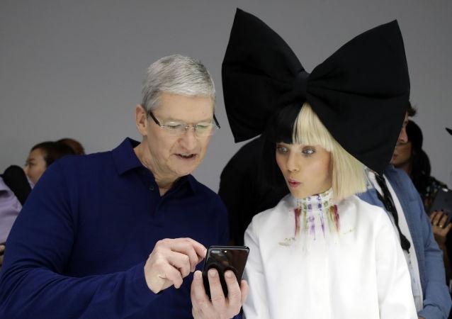 Tim Cook, CEO de Apple, le muestra un iPhone 7 a la célebre bailarina Maddie Ziegler