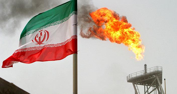 La bandera de Irán con una llama de gas en una plataforma de producción de petróleo al fondo
