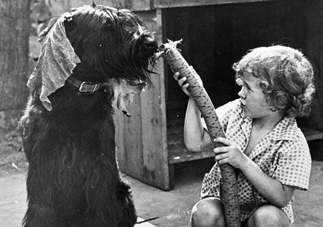 Un niño soviético juega con una aspiradora