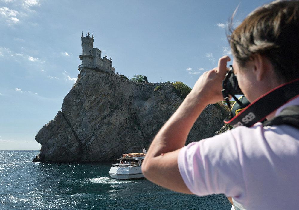 Turista toma foto del castillo Nido de Golondrina desde un barco de recreo.