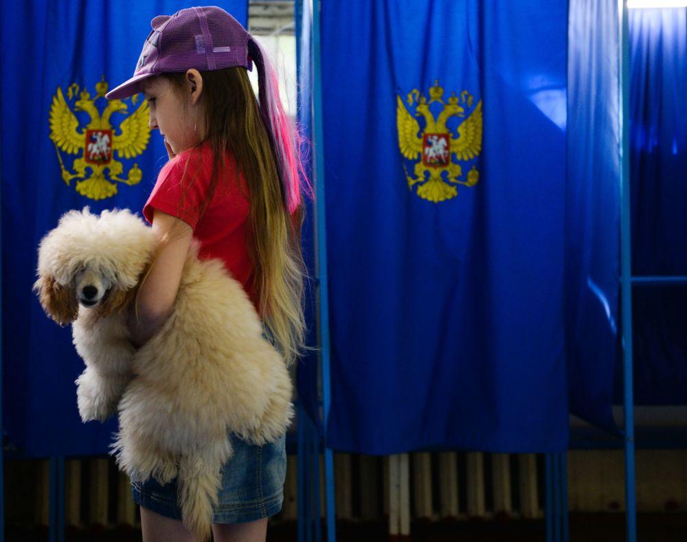 Una niña y su perro, en un colegio electoral en la ciudad rusa de Novosibirsk, durante las elecciones parlamentarias del país eslavo, llevadas a cabo el 18 de septiembre.