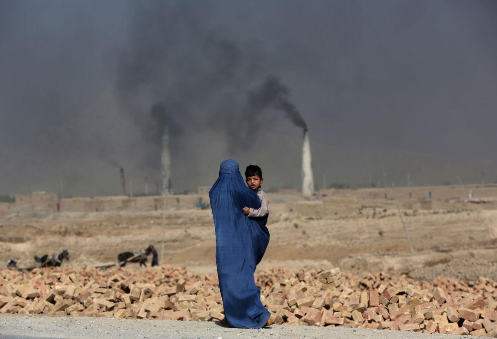 Una mujer afgana camina con su hijo cerca de una fábrica de ladrillos, en las afueras de Kabul.