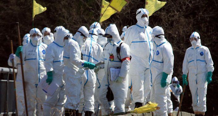 Policías en trajes de protección buscan a desaparecidos en Fukushima