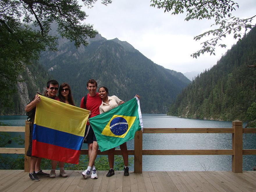 Los viajeros latinoamericanos, Iván, Laís, Felipe y Camila, muestran sus banderas, en China