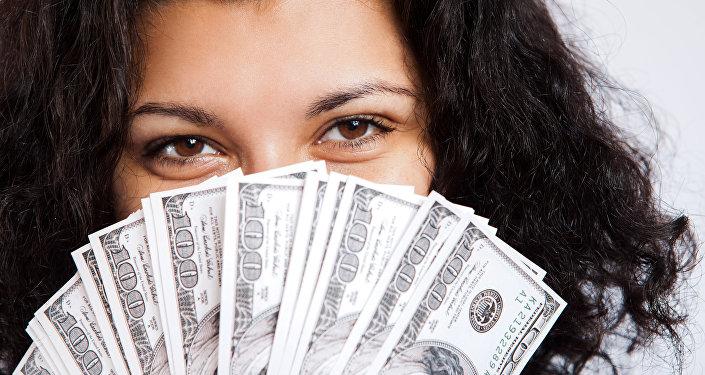 Mujer sostiene dólares (archivo)