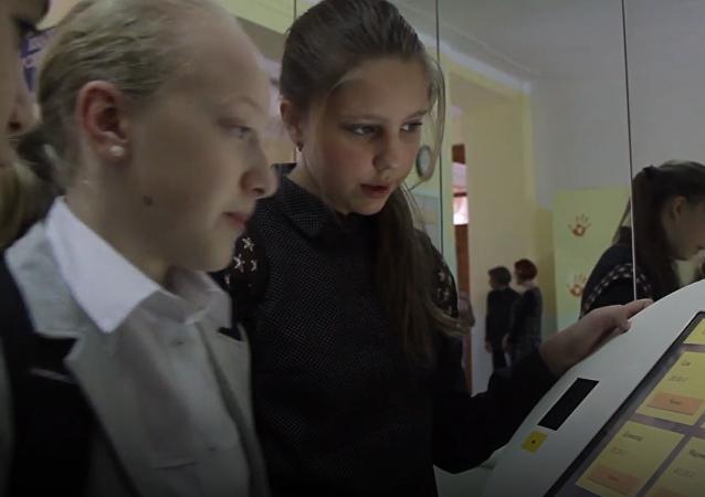 Alumnos de una escuela rusa pagan con la palma de la mano en el comedor