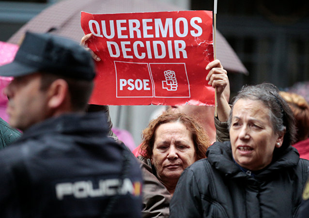 Supporters of Spain's Socialist party (PSOE) hold a poster during a protest outside Spain's Socialist party (PSOE) headquarters in Madrid, Spain
