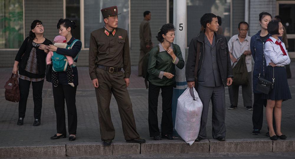 La gente esperando el autobús en una parada de Pyongyang, Corea del Norte