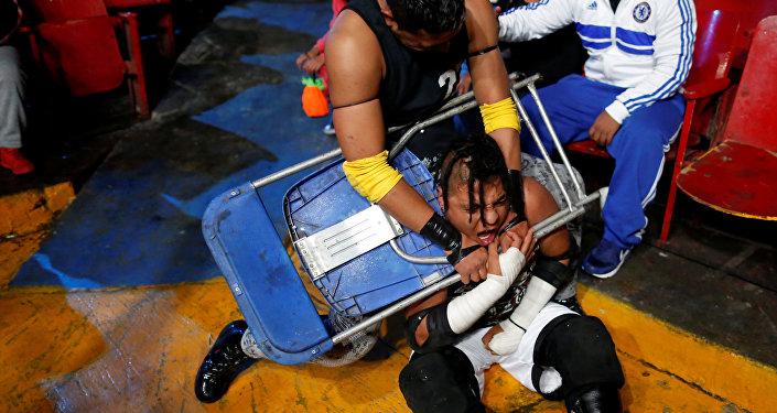 El luchador Gio Malkriado utiliza una silla durante una lucha contra Ciclope