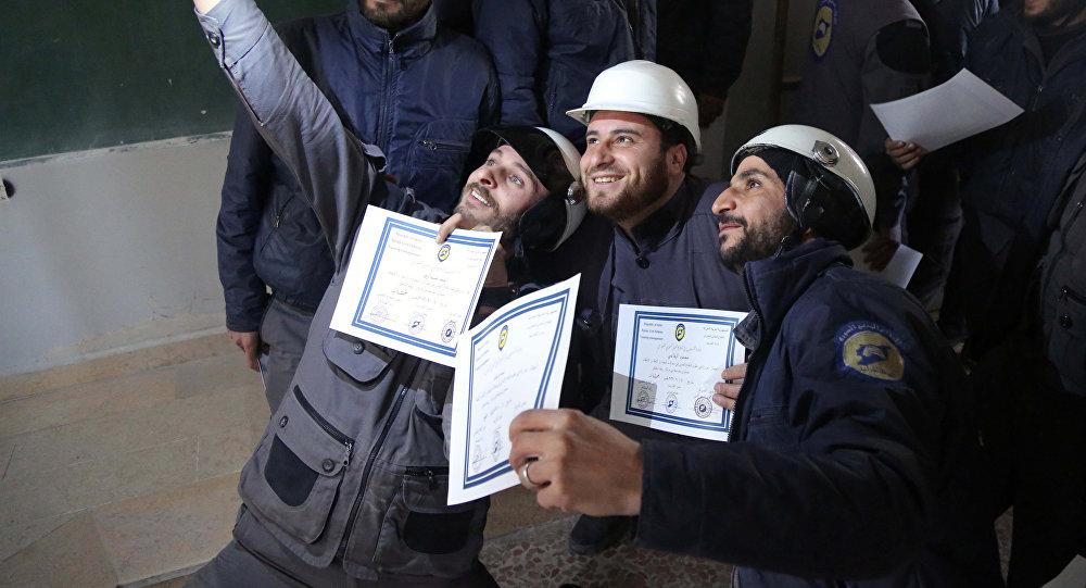 Los miembros de la Defensa Civil Siria, conocidos como los Cascos Blancos, toman un selfie con sus certificados