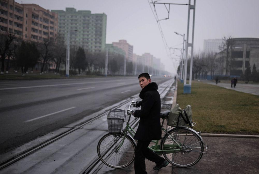 Un joven empuja una bicicleta en una calle de la capital norcoreana