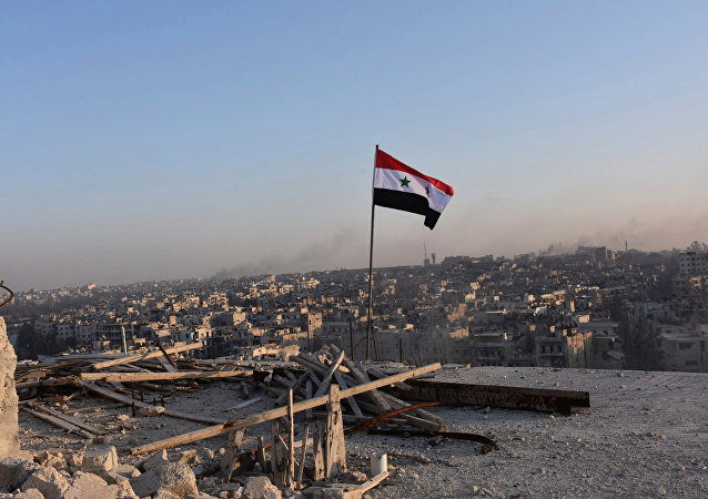 A Syrian national flag flutters near a general view of eastern Aleppo after Syrian government soldiers took control of al-Sakhour neigbourhood in Aleppo