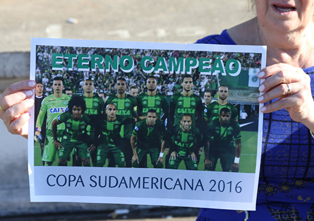 A fan of Chapecoense soccer team shows a poster of her team at the Arena Conda stadium in Chapeco, Brazil