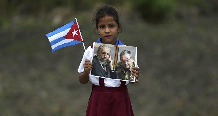 Una niña con las fotos de Fidel y Raúl Castro