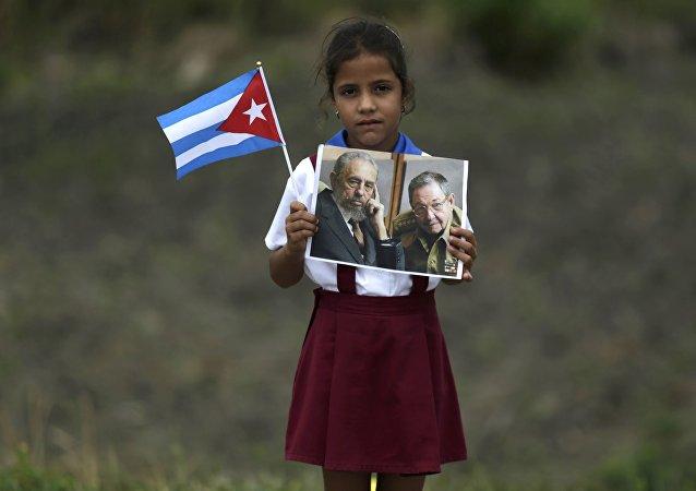 Niña sostiene retratos de los líderes cubanos